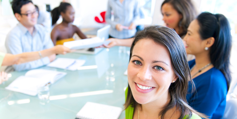 woman smiling with her coworkers at a meeting